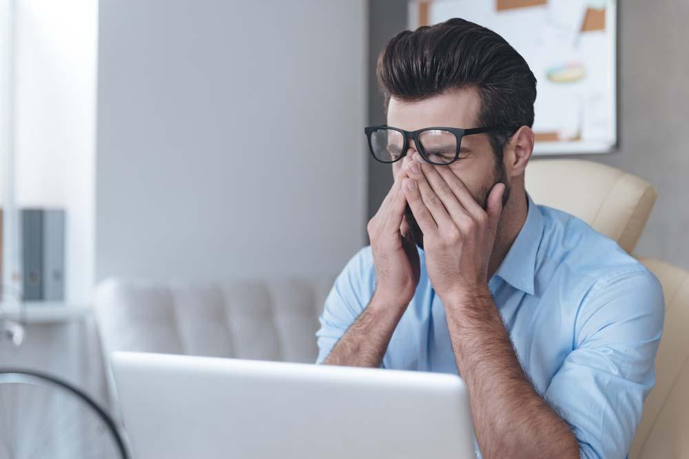 man suffering from staring at the computer for too long