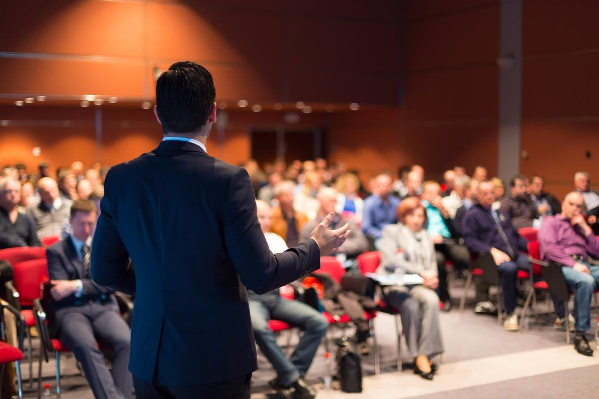 man giving a speech during an Exeter seminar to a room full of people