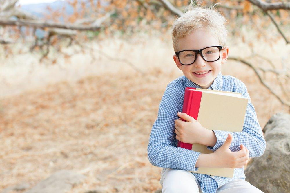 Boy with glasses and a book.
