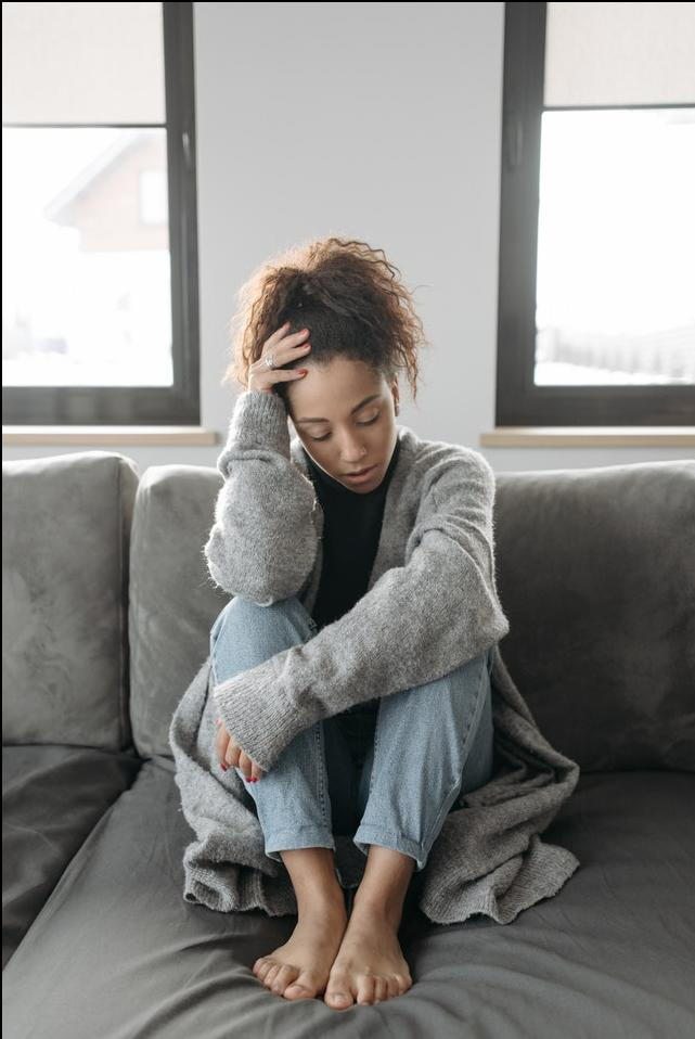 woman sitting on bed with eyes closed and head down in distress