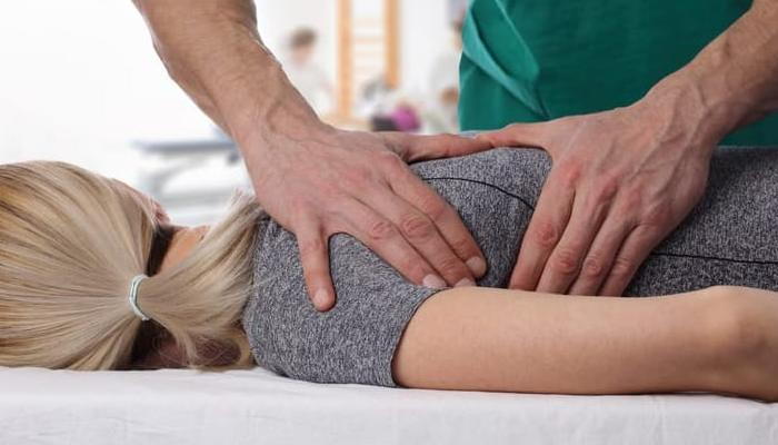 chiropractor adjusting female patients upper back