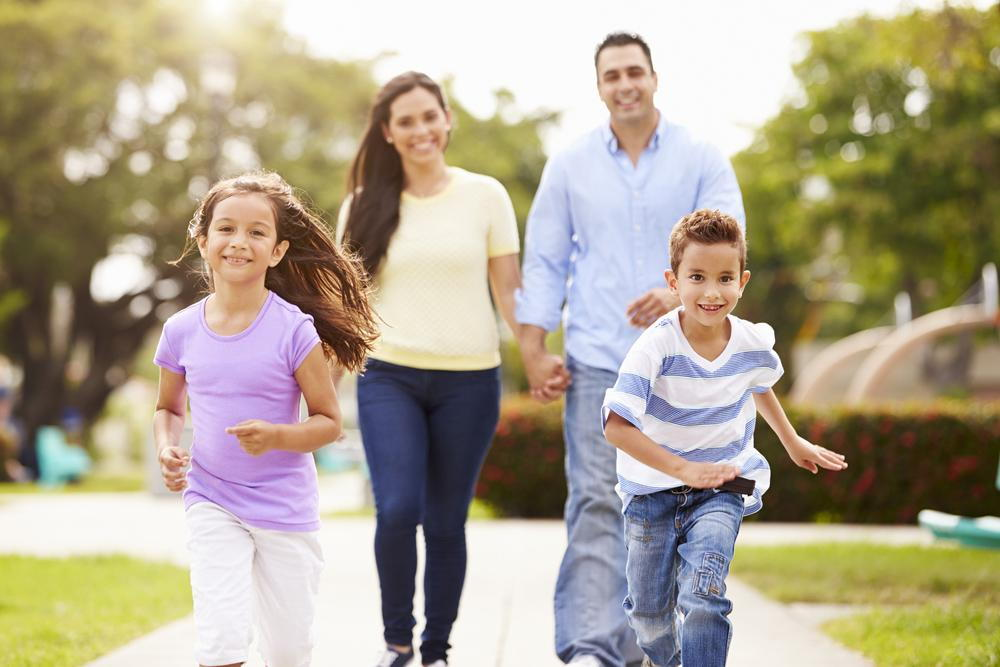 happy parents running with two children who incorporate family chiropractic in Kenosha