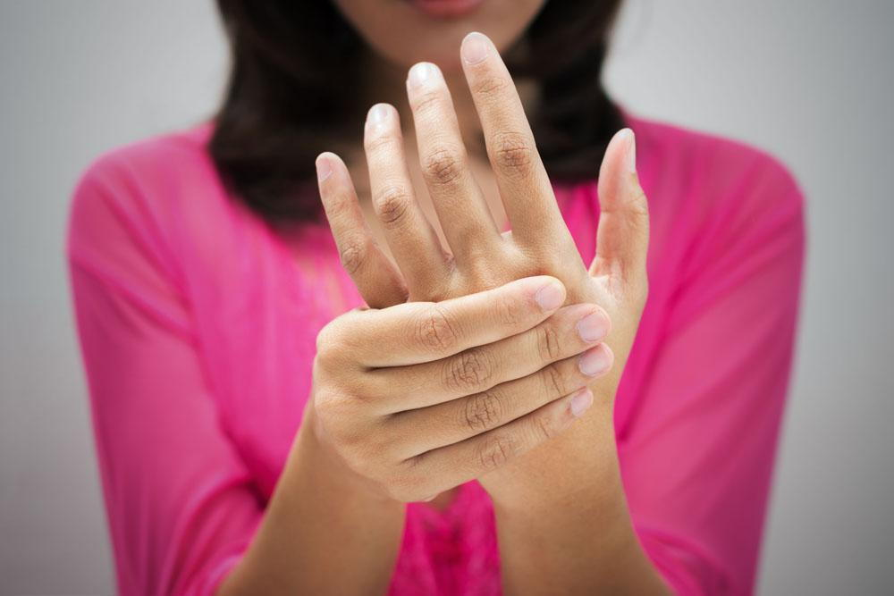 woman holding her hand because of tingling in fingers and numbness in hand