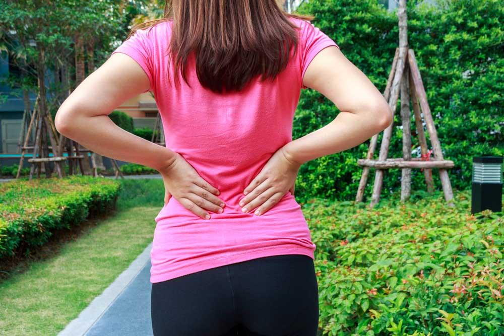 woman suffering from spine pain who could benefit from Pilates and chiropractic care for pain management