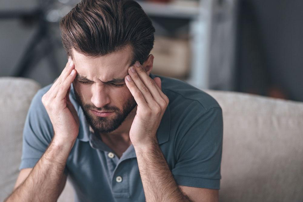man suffering from a painful headache