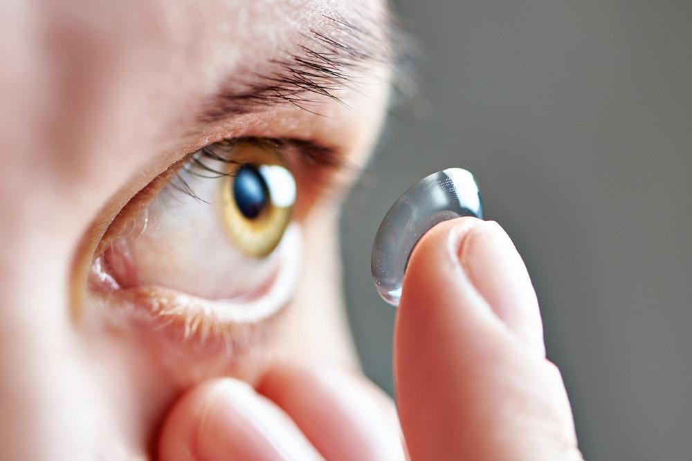 man putting a daily disposable contact lens into his eye