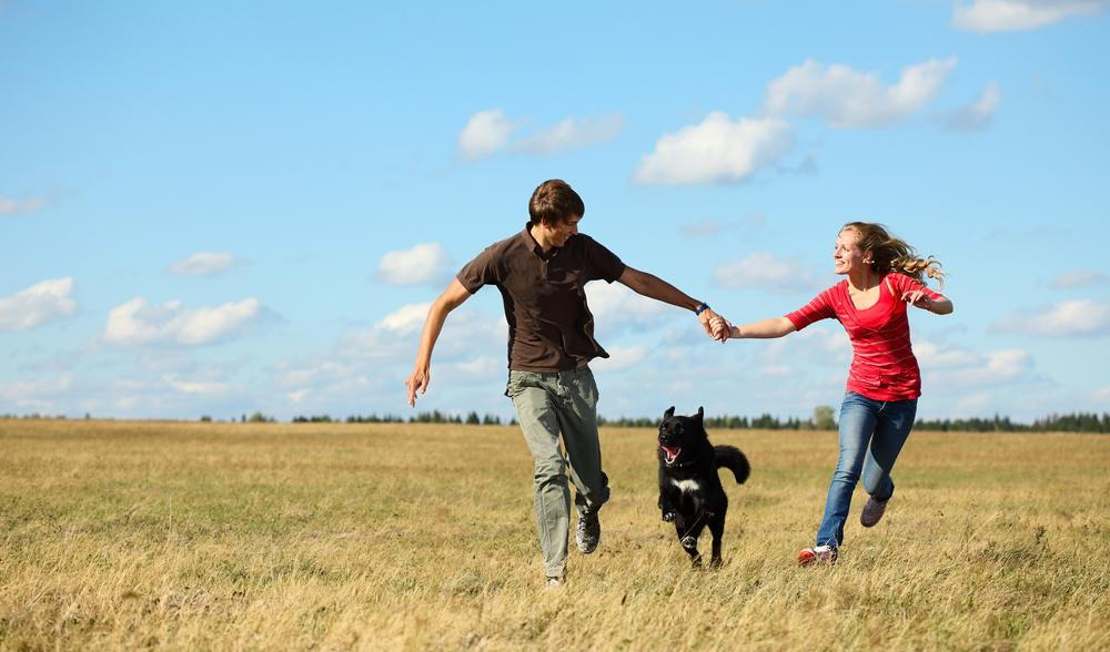 a man and woman running with their dog