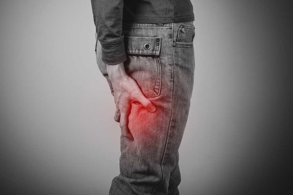 man holding his leg due to sciatic pain