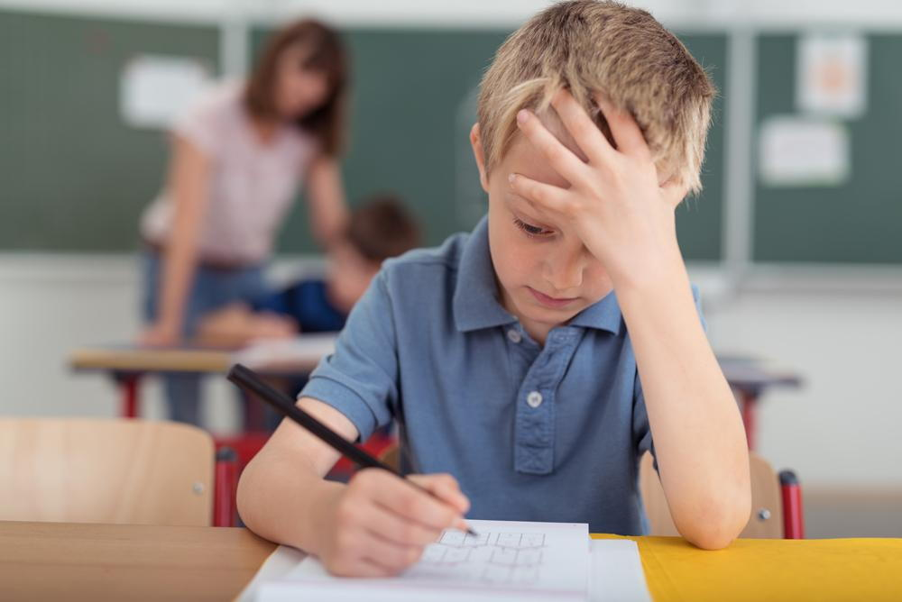 child struggling to do work in a classroom who could have a vision problem and need vision therapy