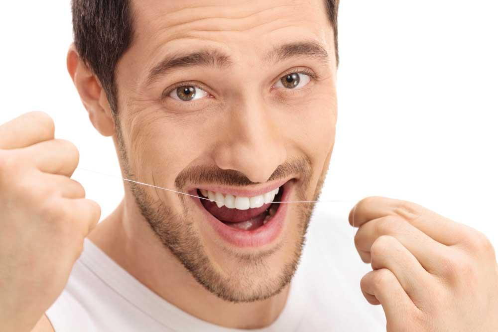 man flossing his teeth to prevent gingivitis