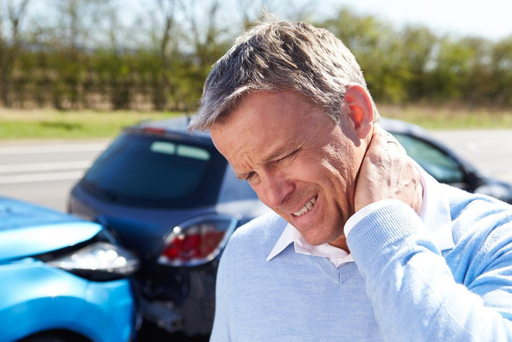 man holding his neck in pain with a car accident in the background