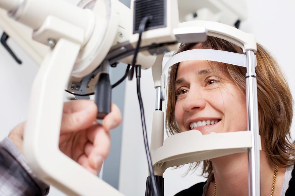 woman receiving an eye exam from her eye doctor