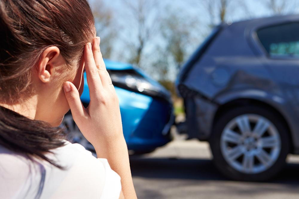 woman holding her head from whiplash pain after an auto accident in Garden Grove
