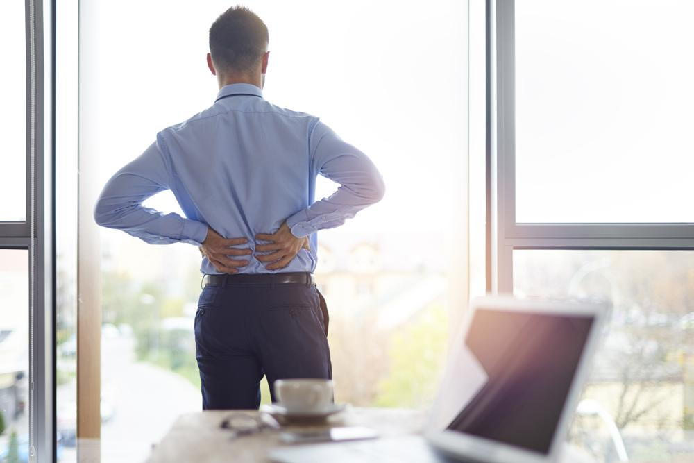 man looking out his window and holding his back in pain from back pain due to poor posture