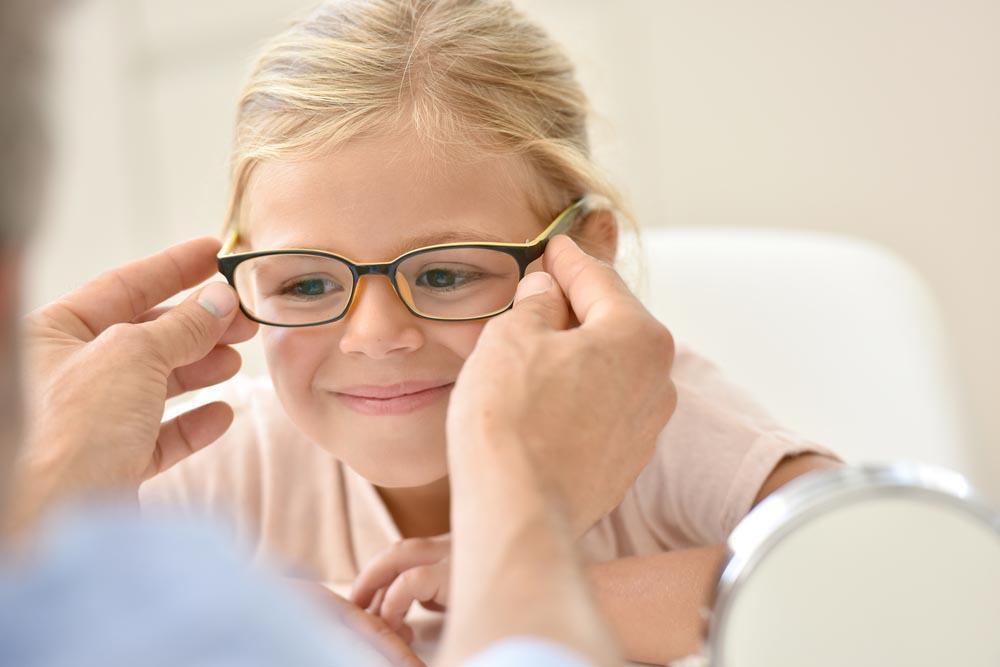 little girl trying on prescription eyeglasses- when should you get reading glasses in Pensacola- Fifty Dollar Eye Guy 5328 N Davis Hwy Pensacola, FL 32503 (850) 434-6387