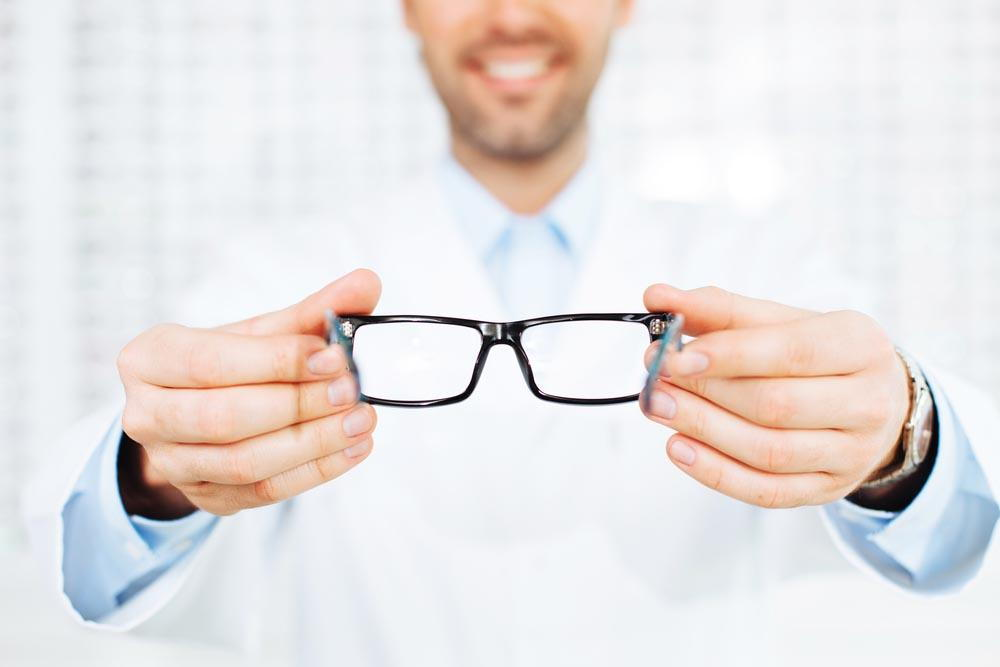 Eye doctor putting glasses on patient-Optometrist Pensacola FL- Fifty Dollar Eye Guy 5328 N Davis Hwy Pensacola, FL 32503 (850) 434-6387