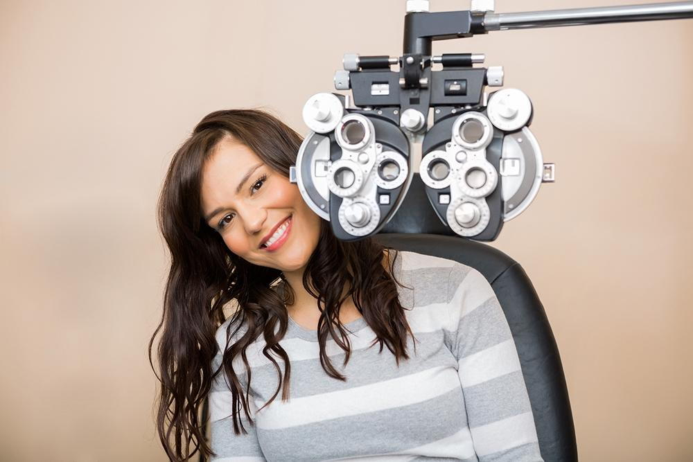 woman sitting in optometry exam chair smiling