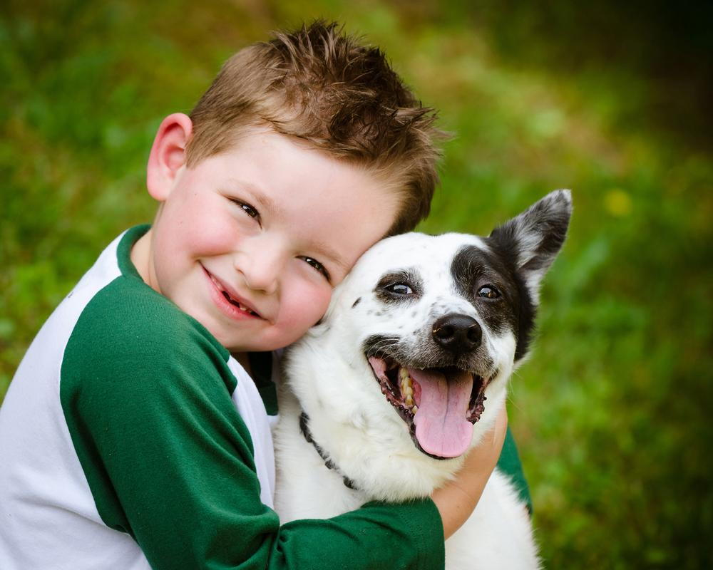 small boy hugging his dog
