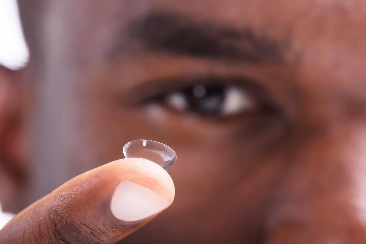man holding a contact lens on his finger