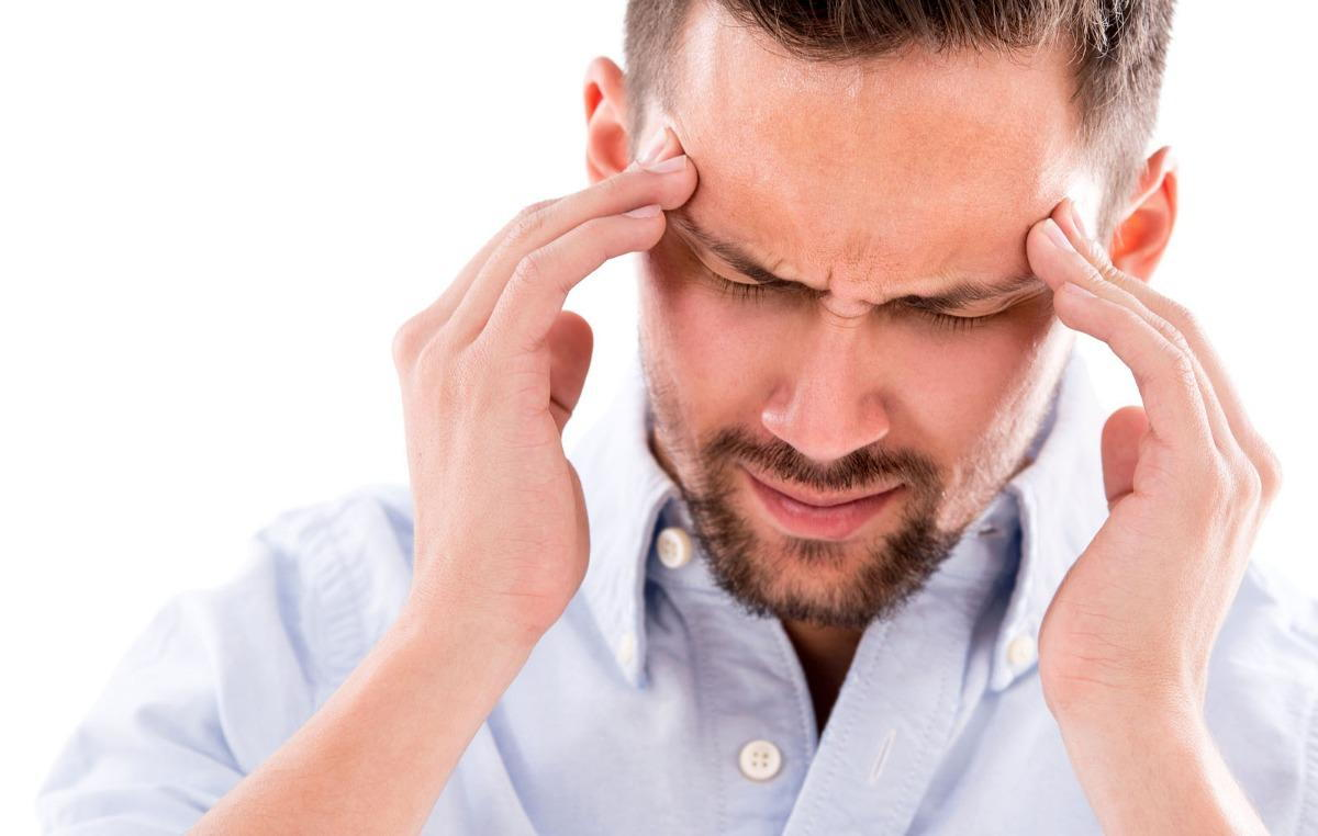 man suffering from a painful migraine