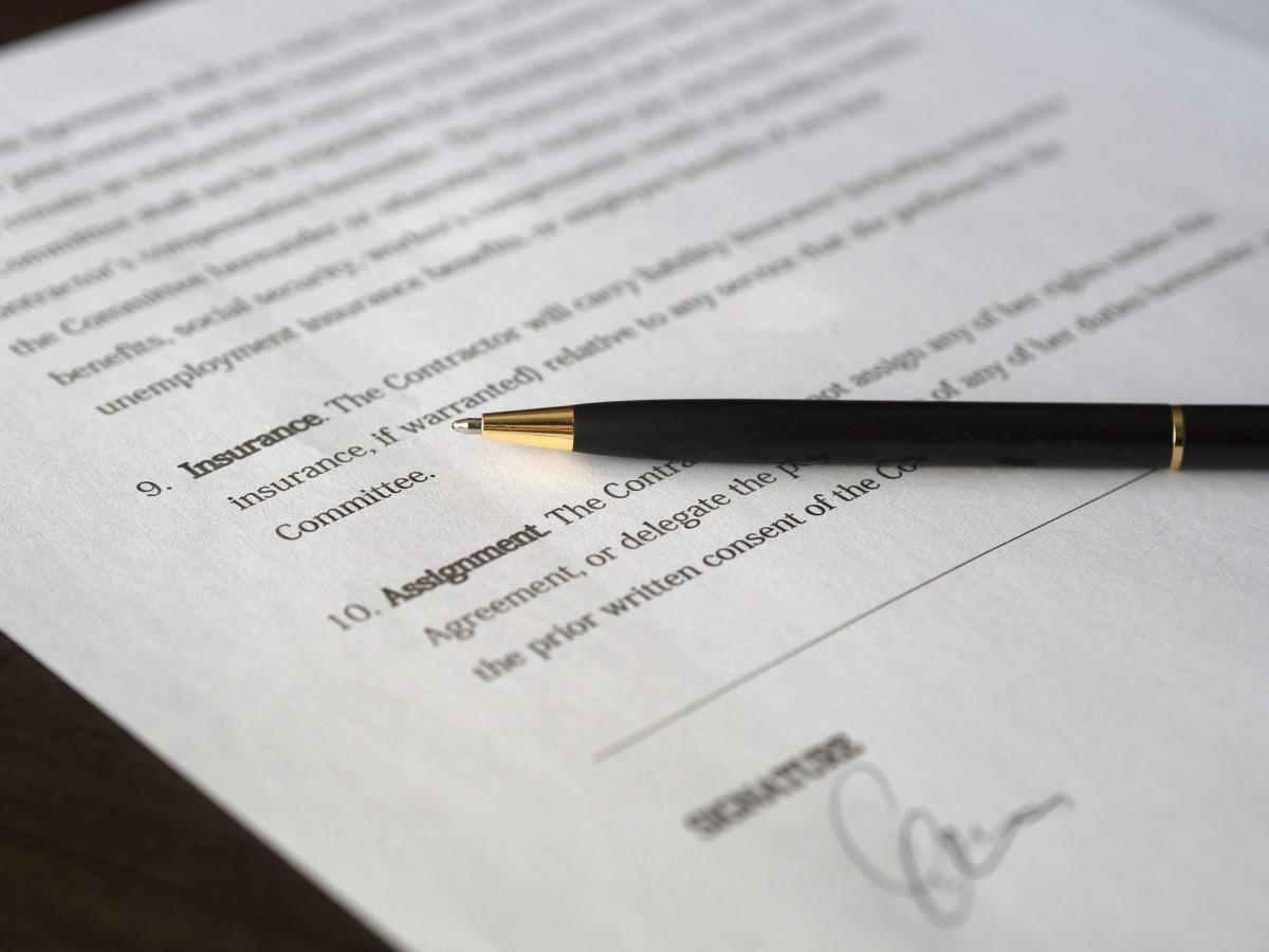 A contract with a pen laying on it