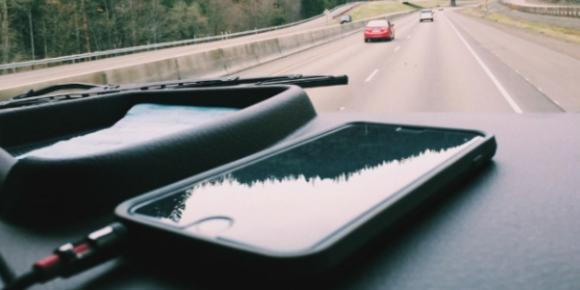 Cell phones rest on the dash of a car traveling down the road