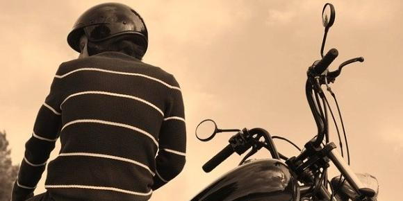A rider leaning on their motorcycle
