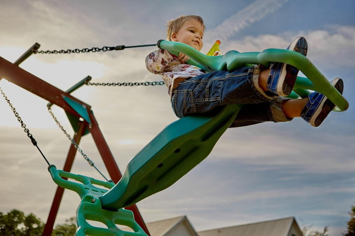A young child using playground equipment