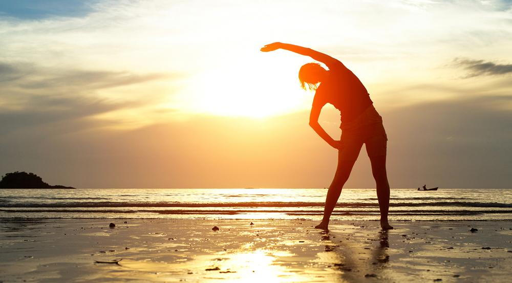 person stretching on the beach at sunset