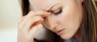 woman feeling stressed and holding her brow