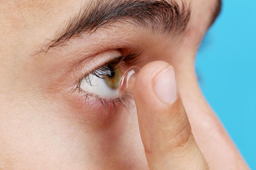 person putting contact lens on eye