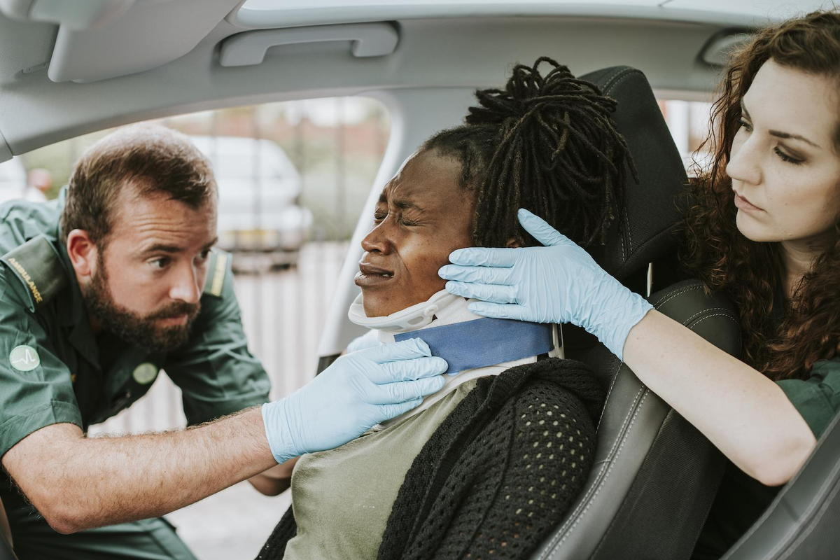 paramedics helping a woman in a car accident