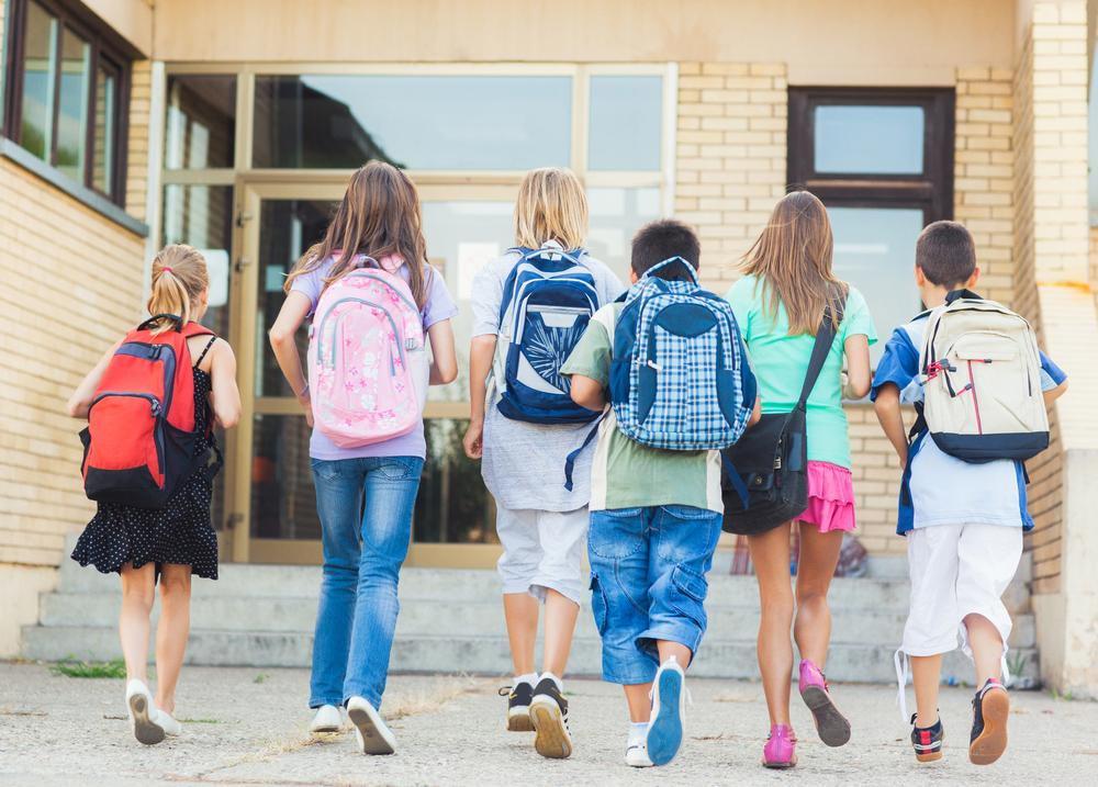 Kids wearing backpacks walking into school