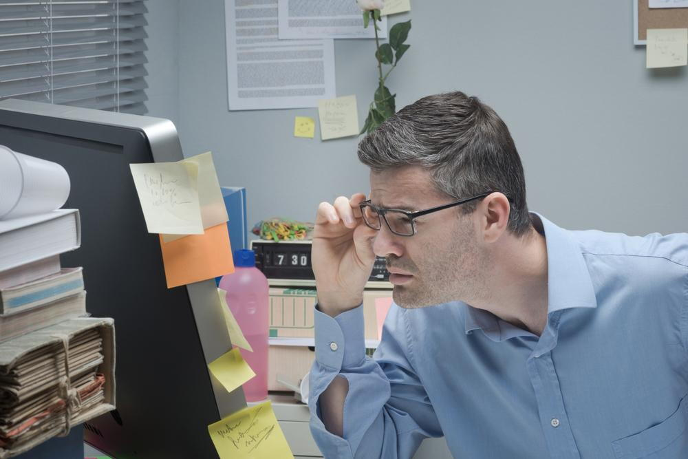 man in his office straining his eyes to see his computer screen