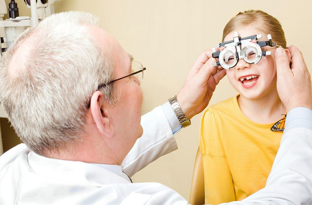 optometrist with child during an eye exam to treat strabismus
