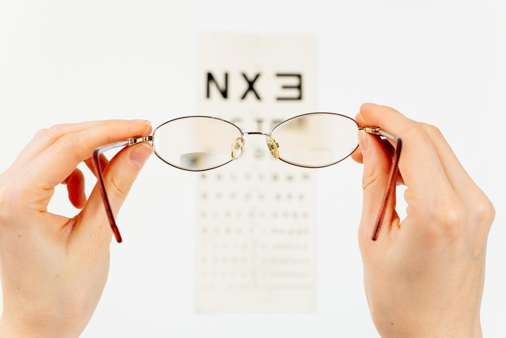 person holding up glasses to see en eye exam chart during an eye exam with her optometrist in Elko