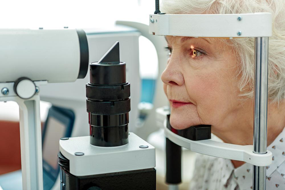 senior female patient during an eye exam with an optometrist in Greenville to screen for cataracts