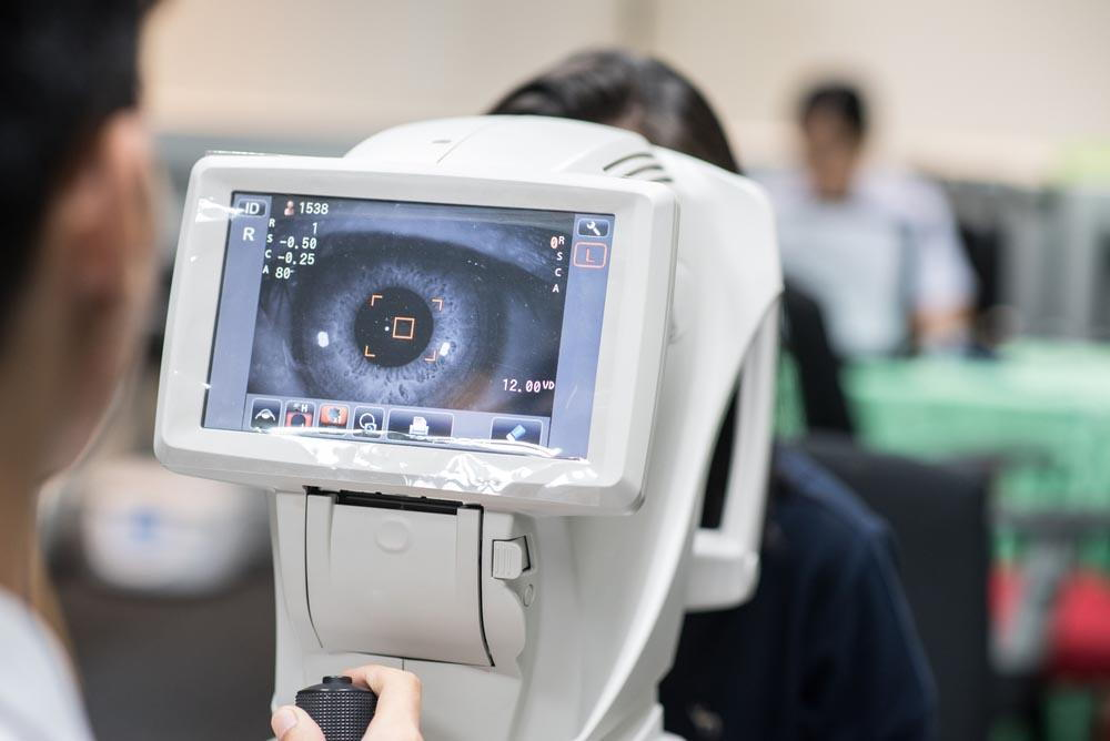 optometrist viewing a ladies eye through an eye machine- Is lassik eye surgery in pensacola worth it- Fifty Dollar Eye Guy 5328 N Davis Hwy Pensacola, FL 32503 (850) 434-6387.jpg