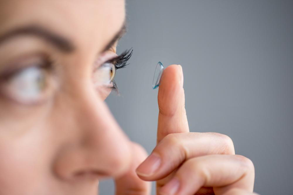 Woman putting on contact lense